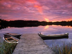 Canoe tied to lakeside dock at sunset in Sweden